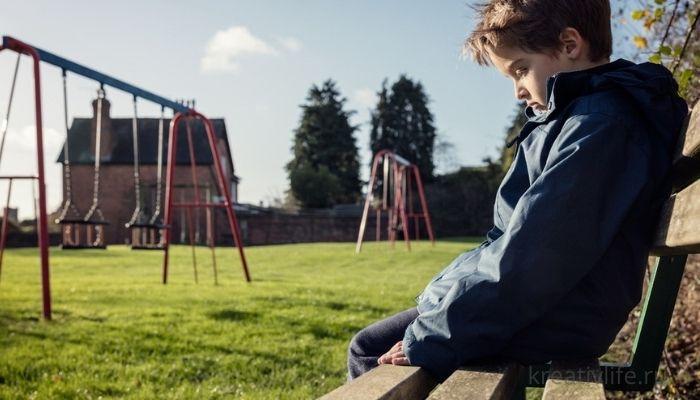 Грустный и печальный мальчтк сиит один на детской плошадке