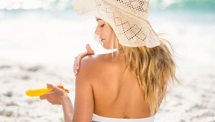Ожог под солнцем. Девушка загорает на пляже и мажется кремом